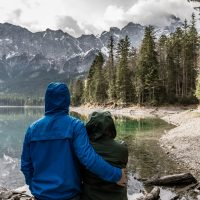 featured photo for this post - a photo of a couple standing in front of a lake with mountains in the background