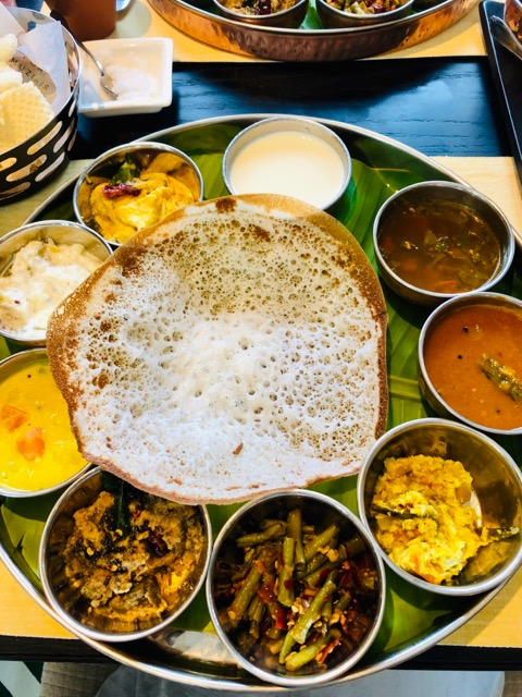 A photo of a thali in Kerala with appam and curries
